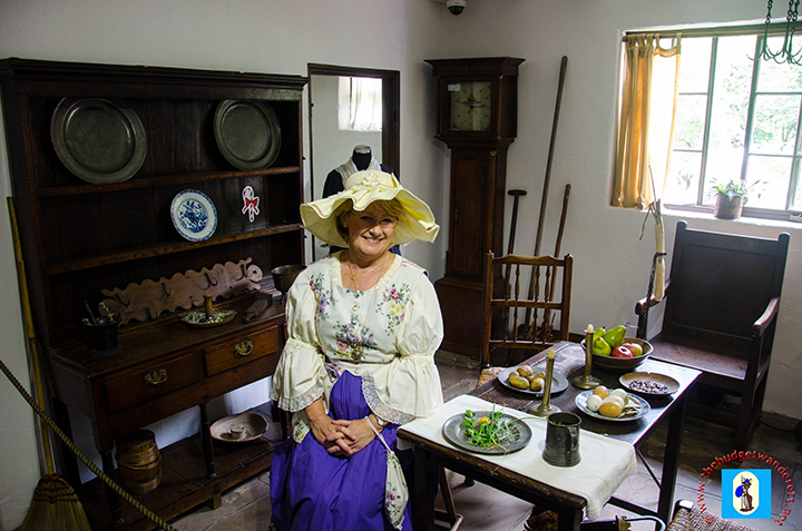 An actress inside the Cook's Cottage.