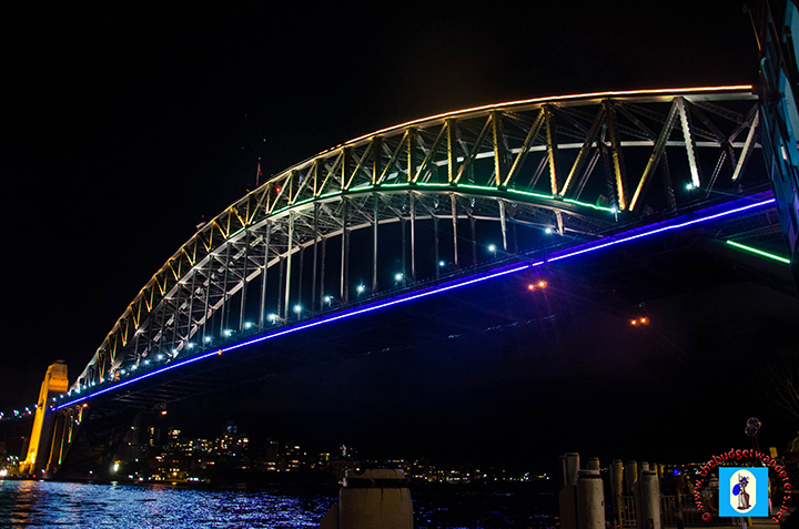 Sydney Harbour Bridge is lit up with colours.